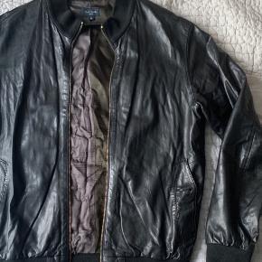 Lækker læder bomber jakke i 100% lammeuld fra Paul Smith. Jakken er i rigtig fin stand men mangler en knap i den ene lomme, det er dog ikke en tydelig detalje. Har to indre lommer :-)