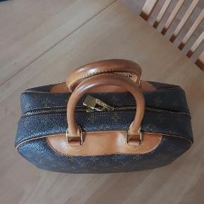 Model Deauville med indvendige stropper, så tasken vil også kunne bruges som toilettaske. Mål : 35 x 26 x 16 cm. Tasken er blevet lidt stiv i læderet, men er stadig en god taske. Der medfølger ikke kvittering, kun dustbag.