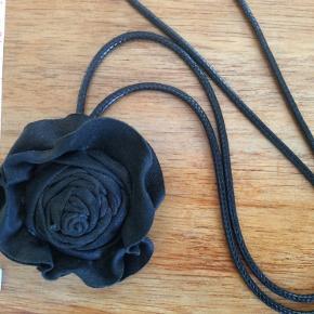 Flot og enkel rosen-smykke i noget skind-materiale. Jeg har aldrig brugt den, har bare lagt i skuffen. Længde ca 92 cm