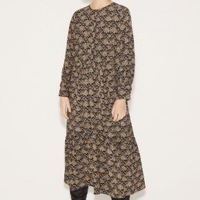 Alaska dress fra Munthe.  Kjolen er i viskose med lange ærmer, rund hals og et flot print på en sort bund.   Længe omkring 123 cm