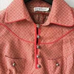 Smuk rød mønstret kjole fra By Groth.  I str. Small – svarer til en str 36. Sælges uden bindebælte. (Der fulgte et silkebånd med, der er blevet væk). Kun prøvet på, har ligget i en kasse og hygget sig lige siden og skal nu videre.