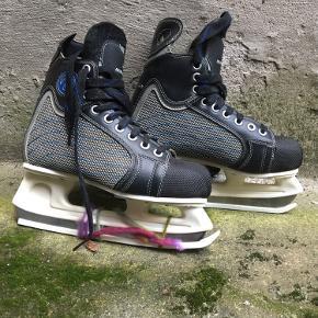 Fede ishockeyskøjter - Revolution T2 i størrelse 41. Er købt for mange år siden, aldrig brugt, men de kan sikkert bruge en kærlig hånd med lidt pleje til skinnerne.  Der er plastikbeskyttere på skinnerne (den ene er holdt fast med noget garn, da den ellers glider af)