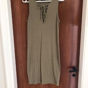 Armygrøn rib kjole uden ærmer i str. M. Kjolen har snøredetalje på fronten. Kjolen er brugt to gange og fremstår derfor som ny.