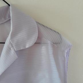 Lækker vintage ærmeløs skjorte i lyselilla stof. Lidt oversized og passer en M/L.