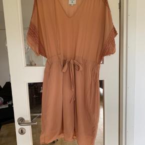 Skøn silke kjole med de fineste broderi detaljer fra Noa Noa The Archive Collection. Let stof en anelse gennemsigtigt, men fungerer super godt med en top indenunder. Kan også bruges af en str. 40 da man kan binde den i taljen. Der er dobbeltlag nederst (fra bindebånd) så man kan se igennem der. 47% silke, 53% viskose.