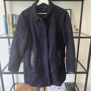 Mørkeblå jakke fra Zara. Går til midt på låret, har lommer og look-a-like-læder detaljer. Rigtig fin efterårsjakke.   Længde foran: 77 cm Længde bagpå: 77 cm Armhul til armhul: 53 cm Indvendig ærmelængde: 42,5 cm