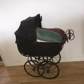 Super smuk antik dukkevogn fra omkring 1930'erne har jeg fået fortalt. Jeg har brugt den som tæppeholder i min stue de sidste par år, men den kan sikkert også bruges til andet.