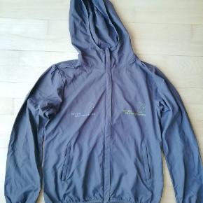 Grå let jakke fra mærket Stella Stanley / Stella Winds med 2 Danmarks Naturfredningsforening logo'er på brystet.