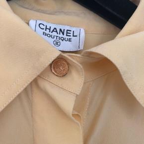 Smuk vintage Chanel skjorte i silke sælges (oprindelse er start 1990'erne).  Skjorten har det ikoniske C-logo som knapper ved hals og ærmer. Ingen størrelseslabel i længere, men den passer både en str. S og M. Sælges til 1100kr afhentet eller plus 33kr i DAO porto.