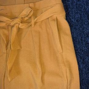 Virkelig fede karrygule bukser fra ONLY. Har stor bindesløjfe, som kan pilles af. Nærmest ikke brugt