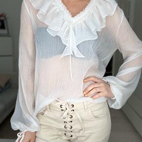 Kun brugt få gange - super fin gennemsigtig bluse med store ærmer og flot krave.