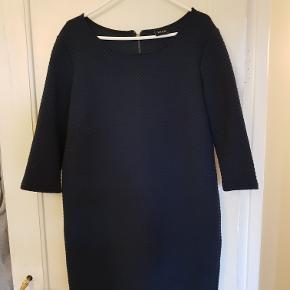 Enkel mørkeblå kjole med mønstret overflade og 3/4 lange ærmer. Lynlås i nakken. 65% polyester/35% bomuld.   Mål Længde: 94cm Bryst: 55cm Talje: 57cm