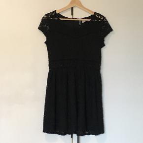 Super fin blonde kjole fra H&M. Kjolen er simpelthen den perfekte lille sorte kjole. Kjolen har korteærmer, og er fuld dekoreret i blonde. Der er små udskæringer omkring taljen som giver en rigtig fin figur!  Kjolen er oprindeligt en str. 40 fra H&M DIVIVED, og derfor er den også en smule lille i størrelsen - den svarer til en normal str. 38-40. Der er ikke særligt meget stræk i kjolen og den lukkes bagpå med en lynlås. Kjolen er brugt få gange til en fødselsdag og konfirmation.