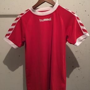 Rød sports t-shirt fra Hummel. Enkelt lille plet i kraven. Skal den sendes betaler køber portoen.