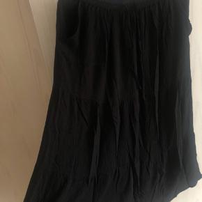 Halvlang sort nederdel med elastik i livet, lommer og bindebånd foran sælges. Den er prøvet på en enkelt gang, men ellers aldrig brugt. Mener det er en str. S/M. Byd