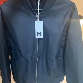"""Martin Asbjørn   Model: Oversized college bomber  """"Navy oversized bomber made from a water-resistant fabric with a matte finish. Double zip closure and front flap pockets. Designed for a loose fit."""""""