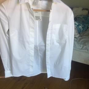 Hvid skjorte med brystlomme i højre side. Ikke brugt, stadig med prismærke.  Str 32 - kan dog passes af en xs