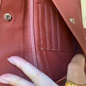 Aldrig brugt. Lækker kalveskinds clutch i mørk rosa. Den er stadig stiv i formen, fordi den aldrig er blevet brugt. Den giver et flot farvepift til et let outfit og er generelt rigtig elegant. Der er en sølv lynlås i toppen, så den er sikker at opbevare værdigenstande i og der er en ekstra lomme til opbevaring af kort.  Mål: 15x24 når den er foldet og 30x24 når den er foldet ud.