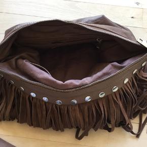 Rummelig taske i blødt skind. Frynser og nitter kan knappes af og der medfølger en kortere rem. Der er et stort primær rum, en mindre lynlåslomme og to mobillommer. H: 27 *W:45 * D:10