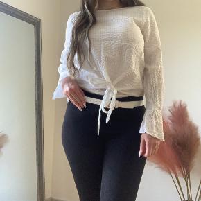 Super sød bluse du kan binde foran og give en fin detalje til dit outfit.  Blusen har elastik ved ærmerne og lukkes med knap i ryggen.   Har en fin længde og kan bruges til både jeans og fx læder bukser   Ts eller mp