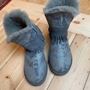 Varme Koalaburra støvler i lammeskind og med frynser, de er grå med pyton print.  Brug dem udendørs eller som hjemmesko. Fast pris.   Tilsvarer UGG støvler. Farven hedder shadow pyton.   Har haft dem på 3 gange indendørs, men de er desværre en anelse for små. Og tro mig: de er dejligt varme. Ingen bytte.   Oprindelig købspris: 1200 kr.