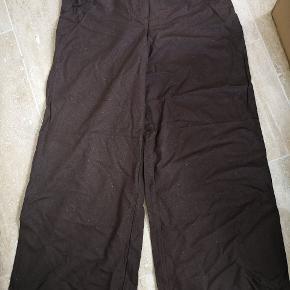 Baggy lign store bukser i 100% naturlig fiber det er derfor ikke støv der ses på billedet men fiber. De har et højt slids på begge ben, hvor der sidder silke stof.