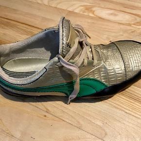 Kategori:  Sneakers - Running Track Shoes   Mærke: Puma  Farve: Guldmetallic med grøn kontrastdesign   Størrelse: 40   Nypris:  900 kr.  nu 150 kr.   Web: puma.com   Silhuet: Flot klassisk pasform med enkelt, elegant og tidløst design, fine detaljer, samt smuk facon.   Andre oplysninger: Se style, model, materialer og rengøringsinstruktioner på nærfoto af tag/mærke. Alle beklædningsgenstande har været renset/vasket siden seneste brug. Herefter er beklædningen almindeligt opbevaret. Men inden du bruger det igen anbefales, at du lufter/vasker/stryger/renser jfr. instruktionerne i mærket.   Bemærk: Evt. bagklædning, bladranke, stol, tørklæde, hat, gine, figur og andet styling medfølger ikke.   Pris: Prisen er voldsomt nedsat, så dette røverkøb er ej til forhandling, ligesom der ikke indgås byttehandler.   Betaling og forsendelse: Jeg sender næsten alt via Trendsales med DAO, køber betaler fragt. Din forsendelse pakkes i praktisk dobbelt plastpose, så den godt beskyttet, samt fylder og vejer mindst muligt.  Hvis der på foto fx er skoæske og anden original emballage medfølger dette naturligvis.   Personlig afhentning: Du er velkommen til selv at afhente i Risskov, Aarhus. Reservation af varen (ved personlig afhentning) kan udelukkende ske mod forudbetaling via MobilePay.   Link til min shop: https://trendsales.dk/p/1749454   Hashtags: #tuesdaysellout #tilsalg #sælges #tøj #jakke #blazer #overdel #woman #frakke #busseronne #skjorte #blouson #bushshirt #kasak #bluse #overdel #kjole #jakke #frakke #robe #kjole #gown #bukser #cowboybukser #jeans #clothes #fashion #bomuld #nylon #polyester #sko #støvler #ankelstøvler #westernskjorte #kimono #cowboyjakke #blazer ting #polo #T-shirt #stiletter