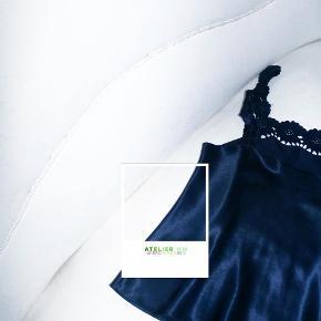 - BENYT 'KØB NU' FUNKTIONEN, VED KØB -  Mørkeblå nattøjsinspireret top. Toppen har en dekorativ blondekant samt stropper, og er i et let materiale med et skinnende finish.   ○ Mærke: Ukendt - intet indvendigt mærke ○ Størrelse: Ukendt - intet indvendigt mærke; ligner dog en str. S (se mål) - Brystmål: 41 centimeter - Taljemål: 43 centimeter - Længde:  56 centimeter ○ Fit: Løs ○ Stand: Brugt og skånvasket meget få gange ○ Fejl/Mangler: Ikke umiddelbart ○ Materiale: Ukendt - intet indvendigt mærke