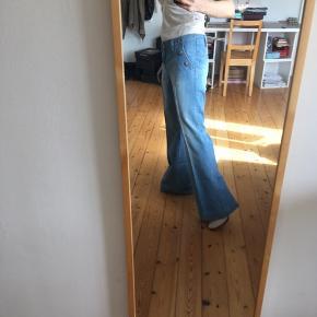 Jeans med flare. Sømandsstil med fine knapper ved lommerne. 70'er stil i pasform. Sidder forholdsvis lavt uden at være lavtaljede.   Aldrig brugt. I perfekt stand.  Sælges også som shorts.