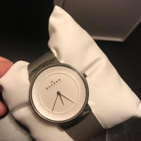 Klassisk Skagen-ur med justerbar stålrem. Minimalistisk, tidsløst design. Sælges i original emballage og med værdibevis.   Uret er brugt, men har ligget urørt i lang tid, da jeg har fået et nyt ur. Det fejler ingen ting og har ingen synlige skader eller ridser.  Sølv og stål.