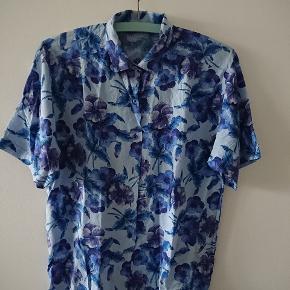 Vintage skjorte bluse med blomster motiv. Farven er knap så lilla, som det ser ud på mine billeder. Passer str M, eller L hvis den skal sidde til