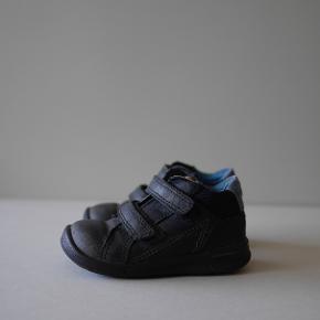 Lækre Ecco sko i blå nubuck skind med fleksibel sål og fast hælkappe. To velcroremme, så de er nemme for barnet at åbne selv. Str. 22. Brugt, men i god stand og perfekte som ekstra sko i vuggestuen. Købt til 599,-