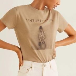 Helt ny T-shirt fra MNG, i 100% økologisk bomuld, tekst på fronten: Sophisticated. Str. Large. Har aldrig været pakket ud og stadig med tags.  Trendsales har gratis forsendelse i efterårsferien 😀