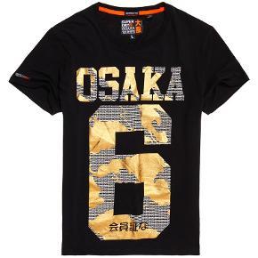 Let Monokrom Osaka T-Shirt  Let Superdry Osaka T-shirt i et monokromt design til mænd. Langærmet T-shirt med rund hals, Osaka grafik på brystet og et lille logomærke på det ene ærme. Tilsætter du slim jeans og sneakers, får du et hverdagslook, der holder maks.  Style: M10103CT Farve: Sort Bomuld 100% C