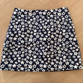 Fin, kort nederdel i jacquard-lignende stof (bomuld/uld/polyester-blanding) med stjerneprint. Lidt lille i str.
