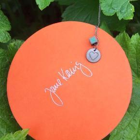 Super fin halskæde i  rhodineret sterlingsølv  fra Jane Kønig med en lille firkløver og et hjerte. Aldrig brugt.   Smykkeæske medfølger.
