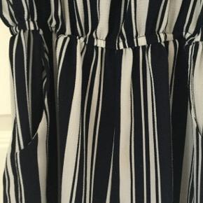 Blå- og hvidstribet.  Polyester og elasthan  Skulderdetalje, flæseærmer, elastik i talje, stiklommer Den er så fin!