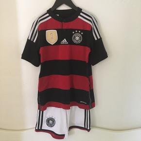Tysk landsholdstrøje fra VM 2014.  Trøjen er i rigtig fin stand og str. 152 (M).   Shorts'ne er str. 140 (S) og følger med gratis pga. standen - der er pletter bagpå - svært at undgå med hvide shorts på en fodboldbane🥴  Sender gerne med DAO😊