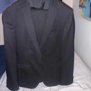 Helt nyt jakkesæt fra Hugo Boss, blot brugt en gang i eget hjem. Jakkesættet fejler intet, og står som helt nyt. Sort med hvide detaljer i stoffet. Slim fit model.