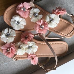 Smukke sandaler med blomsterdesign og perler.