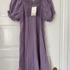 Smuk kjole i den skønneste lilla farve. Den har flæser ved krave og ærmegab.  Prisen er pp