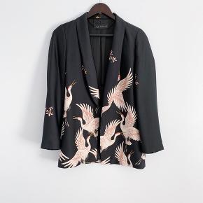 Super flot sort blazer fra ZARA med fugle print i sart Rosa/nude. Satin. Købt i Barcelona til ca 800 kr. Brugt sparsomt og samler derfor blot støv i skabet. Et par fine udtræk i stoffet, som stort set ikke ses (som satin nu gør). Bindebånd er bortkommet