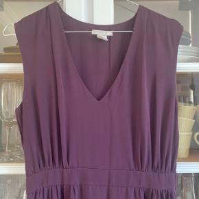 Lang lilla/blommefarvet kjole. Skåret under brystet. Længde fra rygudskæring:  139 cm