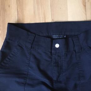 Sorte bukser fra Röhnisch. De er virkelig behagelige på, og har været brugt til golf.  Bukserne har blivet vasket nogle gange, så man kan se at den ikke er helt ny-sort, men farven er stadig fin og den ser ikke slidt ud. 53% bomuld 44% polyamid 3% elesthan