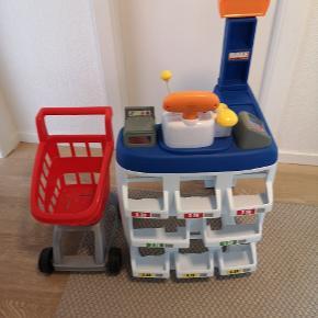 Købmands butik med indkøbsvogn. Der kan følge lidt varer med i form af små æsker, der kan handles med. Kasseapparat er en lille regnemaskine.