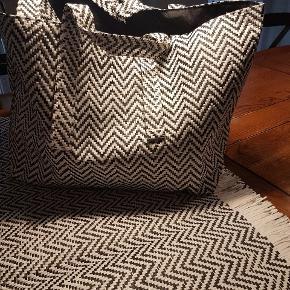 Lækker strandtaske med liggeunderlag/tæppe i sort/hvid. Mærke: Madam Stoltz. Aldrig brugt.