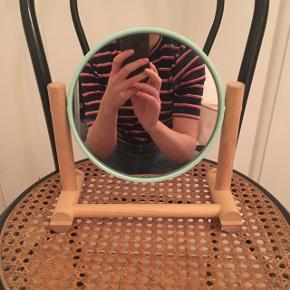 Sødt vippespejl i træ. Selve rammen rundt om spejlet er mintgrøn. Diameter på spejlet er 17 cm. Bredde i alt er 22 cm, højden 23 cm.