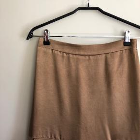 Fin nederdel i silkelignende stof med lille slids og elastik i taljen bagtil.