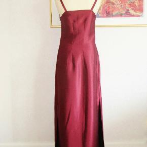 """Størrelse: S/M  Skræddersyet: Lækker lang vinrød kjole med høje slidser (53 cm) i siderne. Materialet er """"thai-silke"""".   Brystvidde: 44 cm x 2 Livvidde: 38 cm x 2 Hoftevidde: 51 cm x 2 Længde: 145 cm.   Ingen byt, og prisen er fast."""