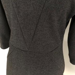 Lækker kjole fra Nümph i mørkegrå meleret.  Kjolen har 3/4 lange ærmer og smarte syninger.  Lukkes med lynlås i ryggen.  Længde fra skulder er 90 cm, brystmålet er 96 cm, og taljen måler 80 cm.  Fremstillet af 57% polyester, 40% bomuld og 3% elastan.  Bærer ikke præg af brug.